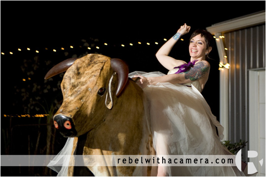 Bride riding a mechanical bull pictures at a wedding  in Columbus Texas for Bret and Estella.