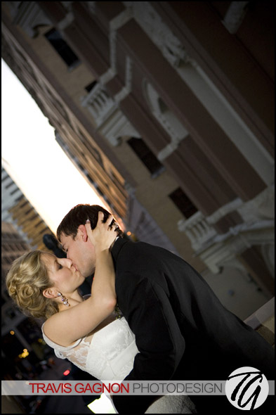 Laura and Justin kiss overlooking 6th street on the balcony during their wedding at the Driskill hotel in Austin, Texas